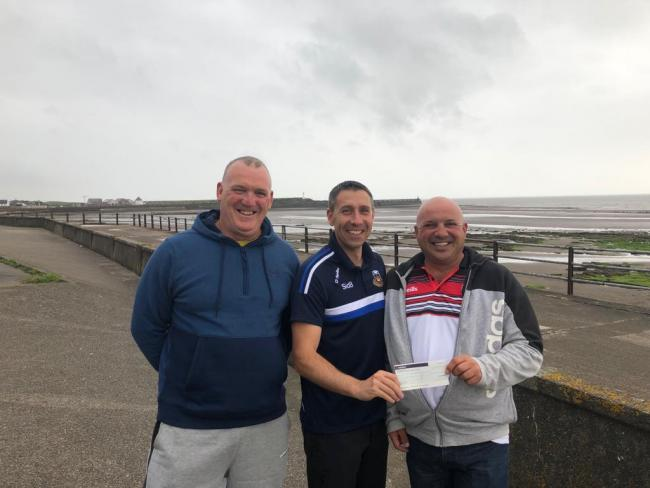 Phil Brown, centre, accepts a cheque on behalf of the Sid 8 Foundation from 