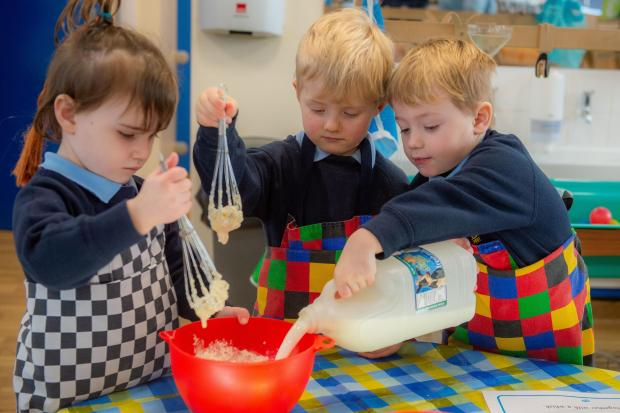 Pancake day at Beckstone School - Archer Lord adds milk as Darcey Bowman and Tommy Braithwaite mix.
