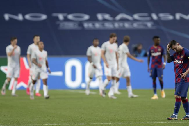 Barcelona's Lionel Messi, right, holds his head as Bayern Munich run riot