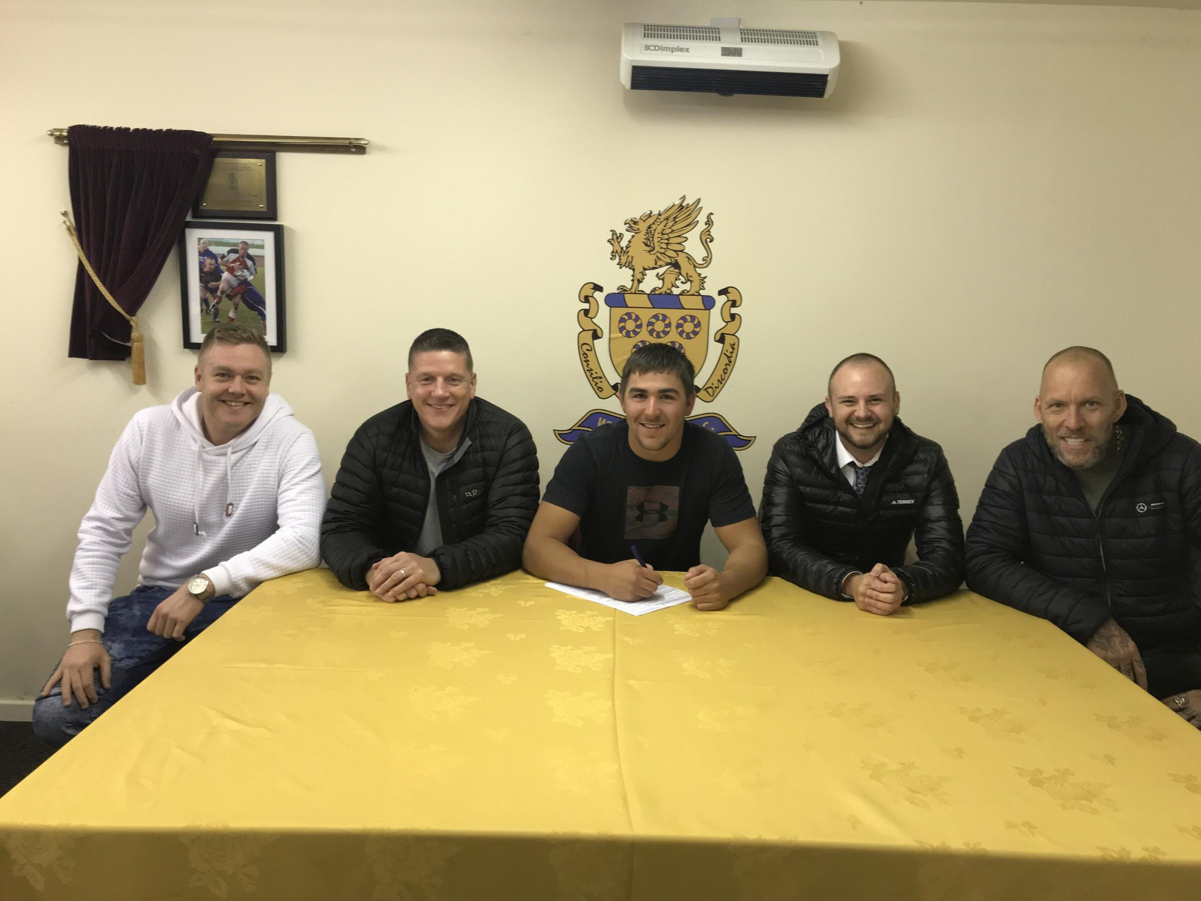 Sam Forrester signs for Whitehaven RLFC watched by, from left, director Andrew Canavan, assistant coach Jonty Gorley and directors Matthew Stephenson and Jason Ball