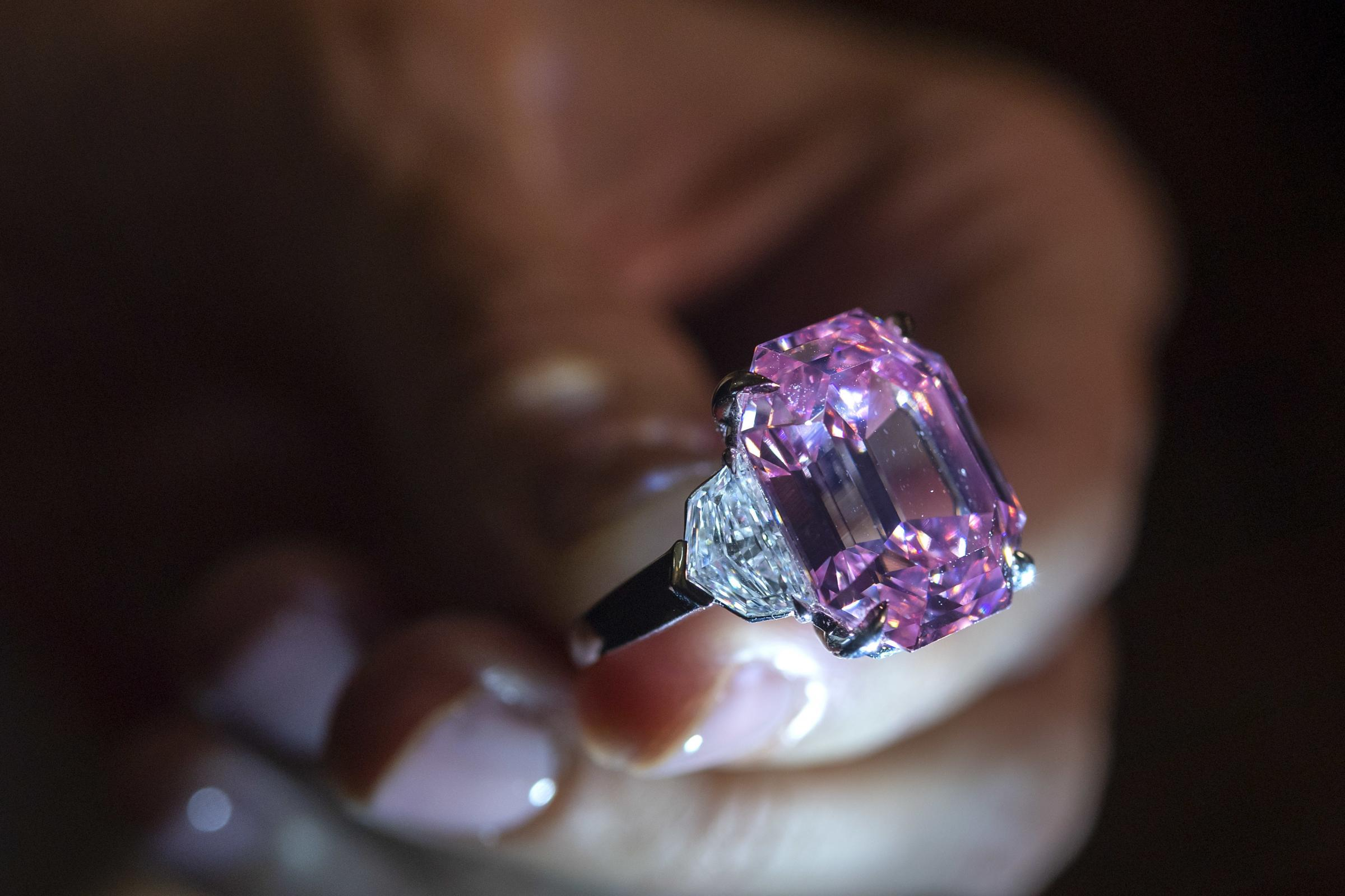 A Christie's employee displays an 18.96-carat fancy vivid pink diamond
